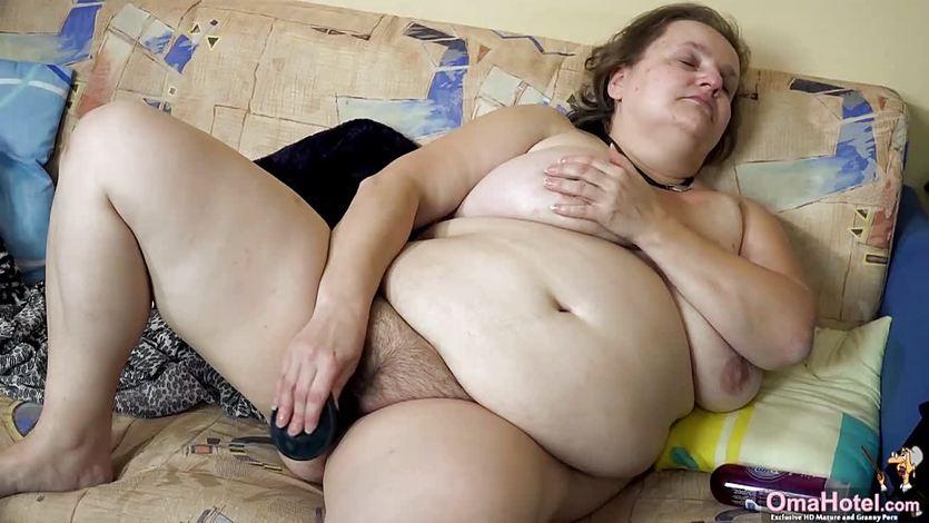 Fette Oma mit Riesenplautze jagt sich Dildo rein